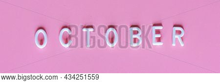Flat Lay Top View Of Word October On Pink Background. October Its Breast Cancer Awareness Month