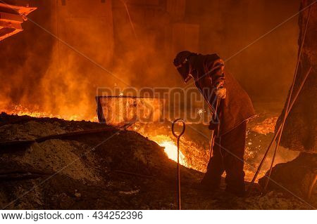 The Process Of Releasing Pig Iron From A Blast Furnace. A Man Works With Molten Metal.