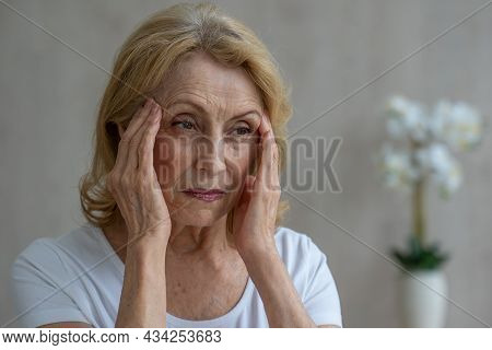 An Elderly Woman Has Headaches, She Touches Her Head With Her Hands, Reports Symptoms Of Dizziness,