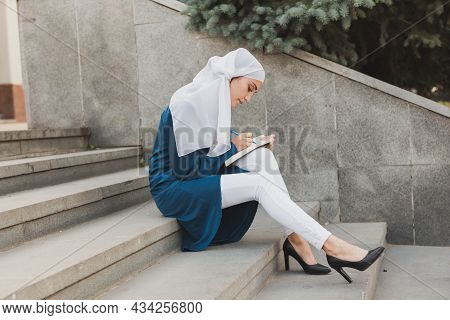 Female Middle Eastern College Student Sits On Stairs In University Campus. Education And Knowledge C