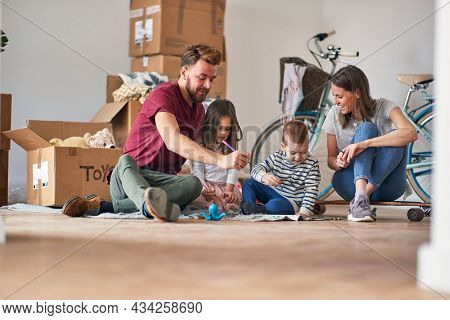 A young family in a relaxed atmosphere is enjoying the new home they have just moved in. Home, family, moving