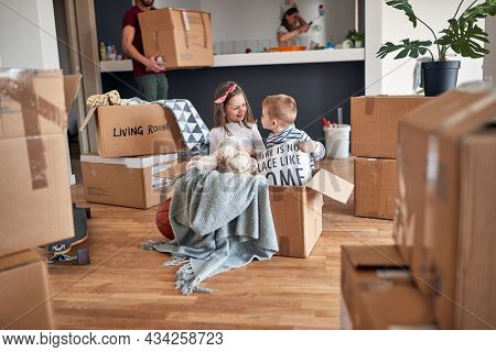 minor caucasian brother and sister, playing in empty cardboard box, happy in new apartment, with their parents in the background. new apartment, new begining