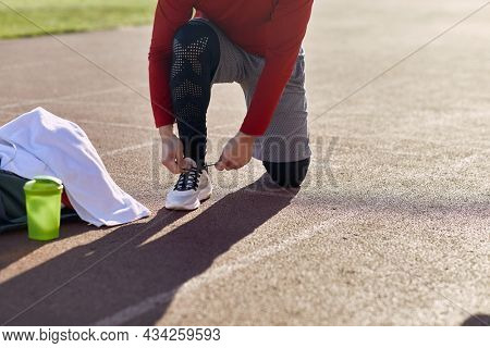 detail, cropped image of caucasian male kneeling on one knee at the stadium athletic track, tying shoelaces, preparing for training. helthy lifestyle concept