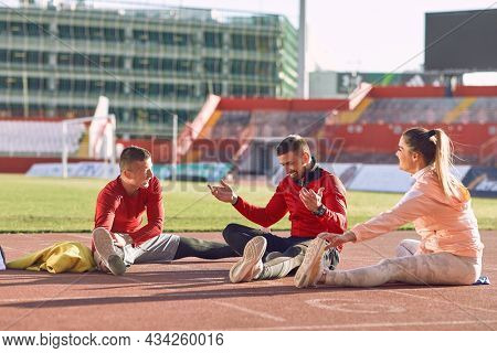 A group of young athletes is warming-up before an athletic training on a beautiful day at the stadium. Sport, athletics, athletes