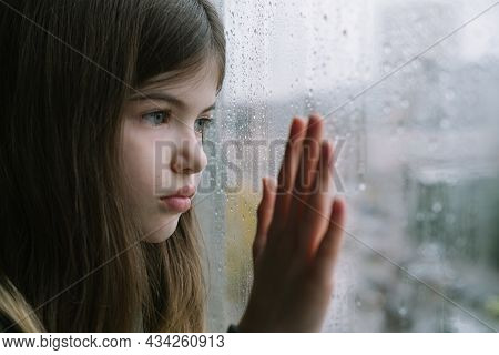 Sad Little, Young Girl Looks Out The Window, Outside The Window Is Raining