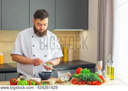 Young Prepares A Poke Bowl In A Modern Kitchen. The Man Prepares Food At Home. Cooking Healthy And T