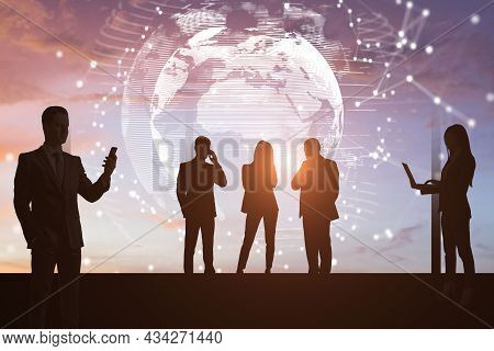 Backlit Businesspeople Using Devices On Abstract Toned Background With Globe And Polygonal Network.