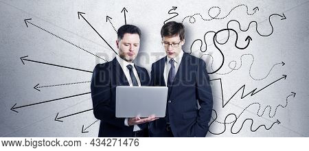 Two Attractive Young European Men Using Laptop Together On Concrete Wall Background With Different A