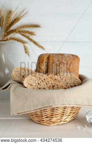 Cut Delicious Ciabatta In Wicker Basket On Beige Wooden Table