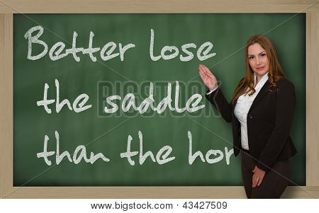 Teacher Showing Better Lose The Saddle Than The Horse On Blackboard