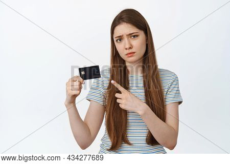 Disappointed Woman Pointing Finger At Credit Card, Frowning And Sulking Upset, Standing Over White B