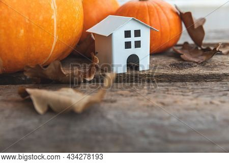 Autumnal Background. Toy House And Pumpkin On Wooden Background. Thanksgiving Banner Copy Space. Hyg