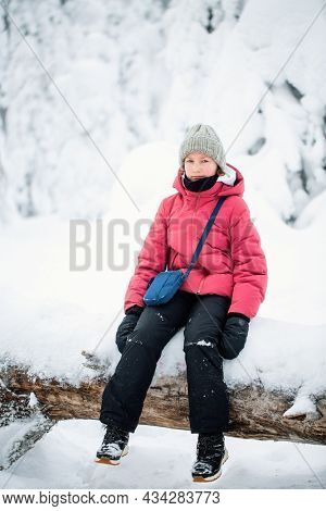 Cute pre-teen girl in winter forest among snow covered trees in Lapland Finland