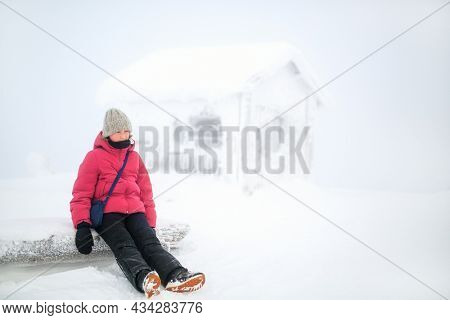 Cute pre-teen girl resting next to snow covered hut in Lapland Finland