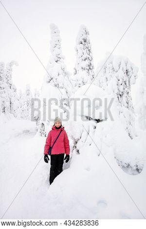 Cute pre-teen girl next to funny snow ghost tree in winter forest in Lapland Finland