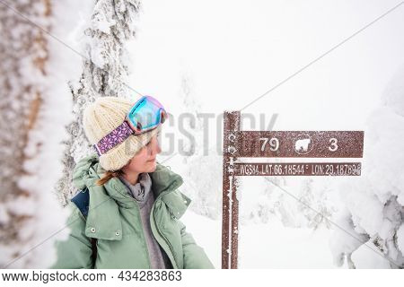 Young beautiful woman next to signpost on Valtavaara winter hiking trail in snow covered forest in Lapland Finland