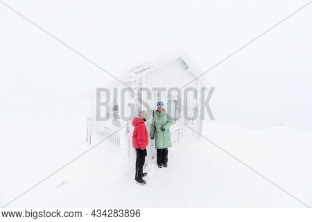 Family of mother and daughter walking next to snow covered hut on winter day in Lapland Finland