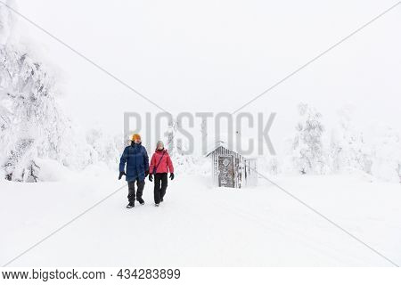 Family of father and daughter walking next to snow covered hut while hiking in beautiful winter forest in Lapland Finland