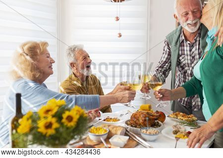 Two Senior Couples Gathered For Thanksgiving Dinner, Host Expressing Gratitude To His Wife For Makin