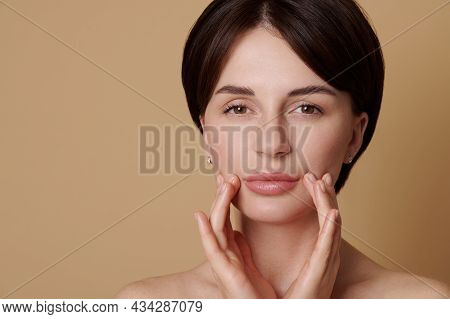 Beauty Portrait Of Half Naked Caucasian Young Gorgeous Woman Massaging Her Face, Looking Confidently