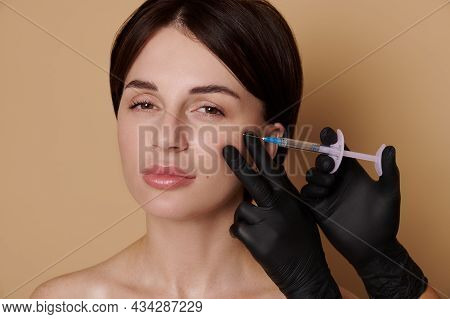 Young Brunette Woman Receiving Anti-aging Rejuvenating Treatment. Hands In Medical Gloves Making Hya