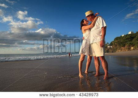 Mature senior adult couple kiss on tropical beach standing in ocean water.