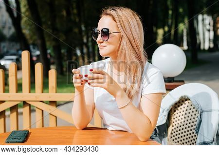 Portrait Of Beautiful Fashionable Young Woman In Glasses Holding Cup Of Coffee While Relaxing In Str