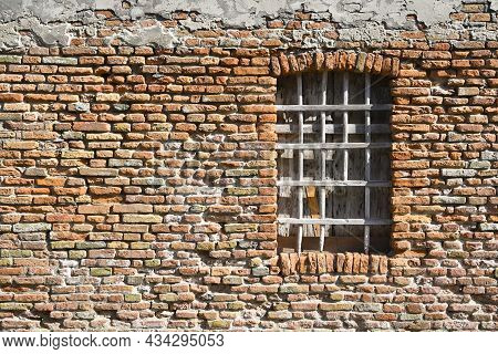 Boarded Up Window With Wooden Bars In An Old Shabby Brick House