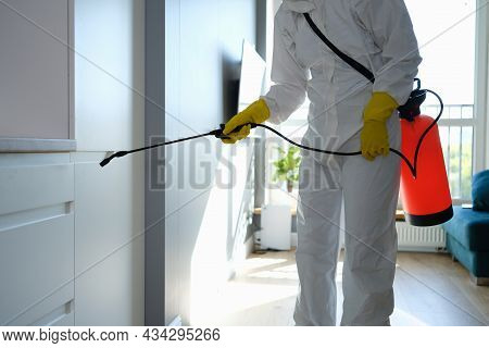 Worker In Protective Overalls And Gloves Disinfecting Apartment