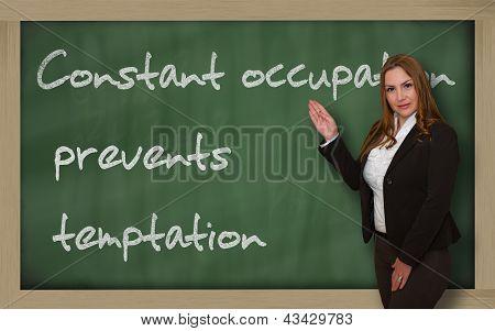 Teacher Showing Constant Occupation Prevents Temptation On Blackboard
