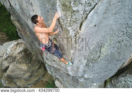 Determined Climber Clambering Up Steep Wall Of Rocky Mountain. Sportsman Overcoming Difficult Route.