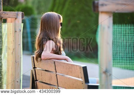 Lonely Woman Sitting Alone On Lake Shore Bench On Warm Summer Evening. Solitude And Relaxing In Natu