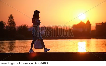 Lonely Pedestrian Woman Walking Alone On Lake Side On Warm Evening. Solitude And Relaxation Concept.