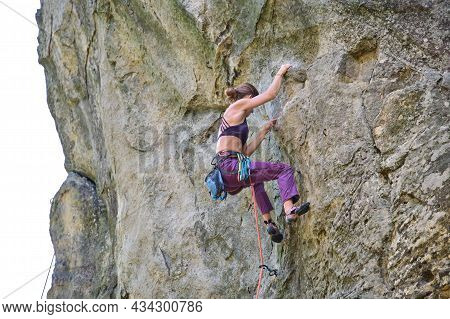 Strong Female Climber Climbing Steep Wall Of Rocky Mountain. Sportswoman Overcoming Difficult Route.