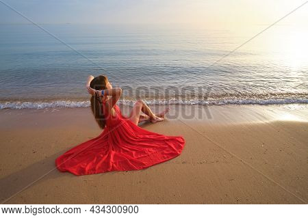 Young Happy Woman Wearing Red Dress Resting On Sea Beach Enjoying Warm Summer Morning.
