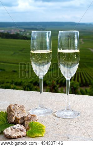 Glasses Of Brut Champagne Wine, Firestones From Vineyards Soil And View On Grand Cru Vineyards Of Mo