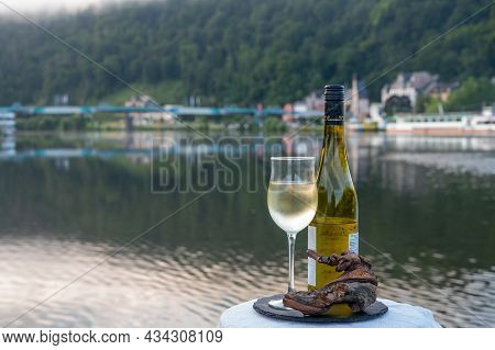 Tasting Of White Quality Riesling Wine Served On Outdoor Terrace In Mosel Wine Region With Mosel Riv