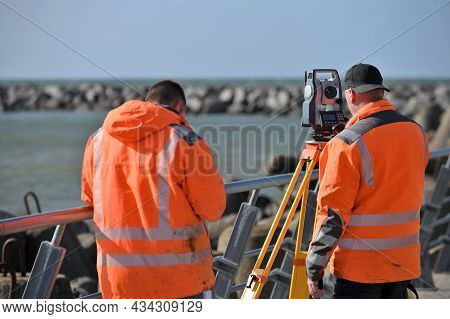 Surveyor Workers With Geodesy Equipment Device, Theodolite At Land Surveying Outdoors