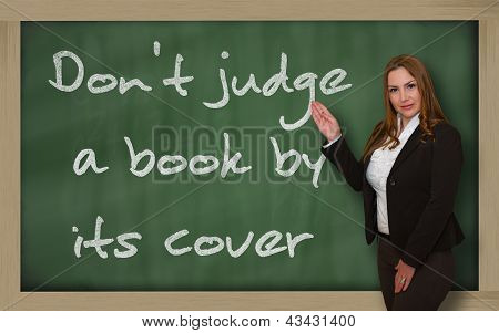 Teacher Showing Don't Judge A Book By Its Cover On Blackboard