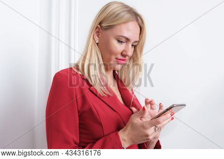 Portrait Of Attractive Young Blond Woman In A Red Blazer. Woman Holds A Smartphone In Her Hands And