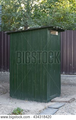 An Open-air Rustic Toilet, A Traditional Wooden Country Toilet Painted With Green Paint
