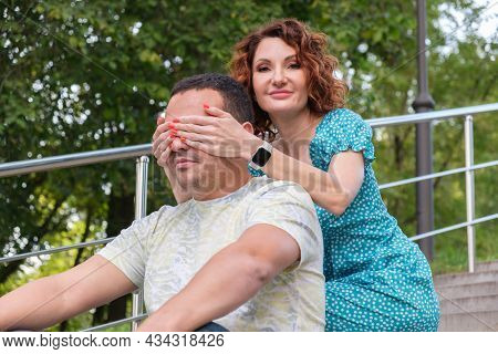 Curly Red-haired Woman Came Up To Man From Behind And Covered His Eyes With Her Palms. Wife Flirts W