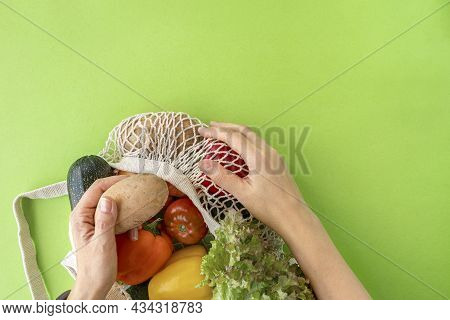 Top View Of Female Hands Reaching For Organic Eco Vegetables From Mesh Shopping Bag On Green Backgro