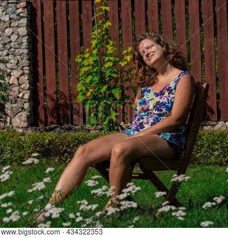 Young Woman Sunbathing While Sitting On A Chair In The Garden