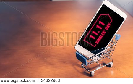 Smartphone With 11.11 Message On Screen Inside A Small Shopping Cart, Singles Day Online Shopping Co