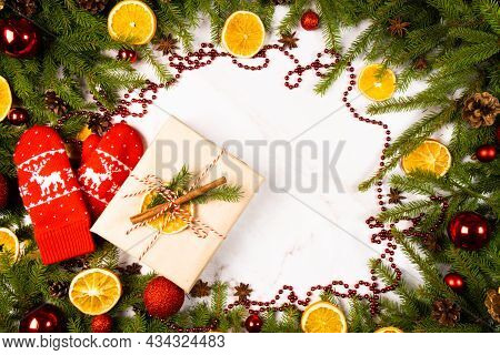 Branches Of A Christmas Tree With A Gift Box, Cones, Christmas Balls , Slices Of Orange And Red Chri