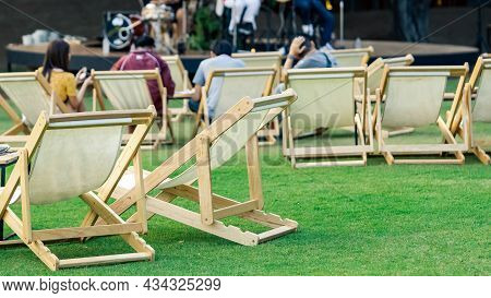 Many Empty White Deck Chairs With Tables For Dinner In Lawn Is Surrounded By Shady Green Grass. Comf