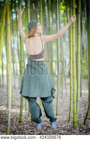 Hip-hop Girl In A Tank Top With An Open Back Stands In A Bamboo Grove Holding Green Trunks