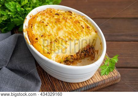 Homemade Shepherd\\\'s Pie in the casserole dish on a dark wooden background. Traditional British dish with minced meat and mashed potatoes.