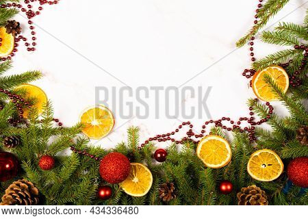 Branches Of A Christmas Tree With Cones, Christmas Balls , Slices Of Orange And On A Light Backgroun